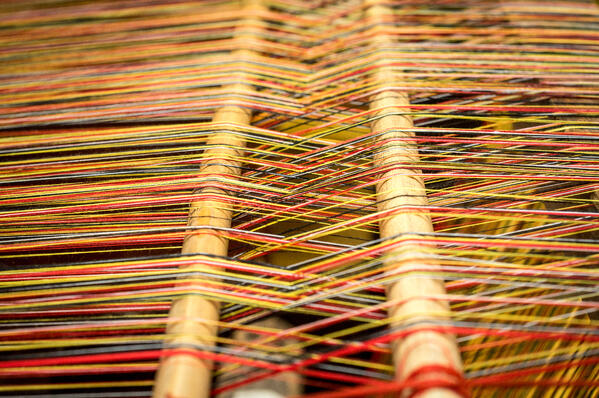 close-up-of-brocade-fabric-weaving-on-loom-cotton-on-the-manual-wood-loom-traditional-axminster-carpet